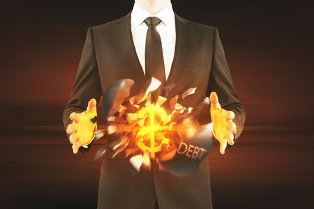 repossession: Debt concept. Businessman holding exploding wrecking ball with golden dollar sign inside on dark background