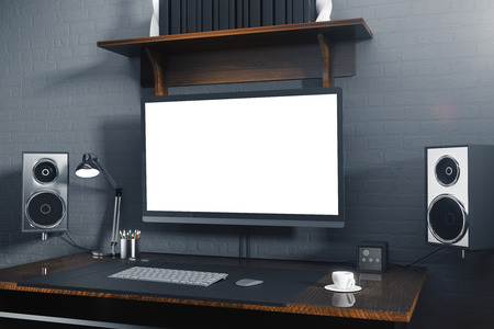 Front view of creative hipster desktop with blank white computer screen, speakers, coffee cup, keypad and other items. Mock up, 3D Rendering