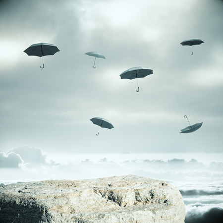 financial cliff: Cliff and falling umbrellas on dull sky background. Safety concept