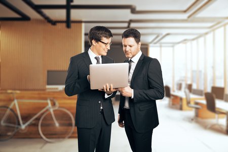 Two handsome caucasian businesspeople using laptop in modern office. Meeting and teamwork concept Stock Photo