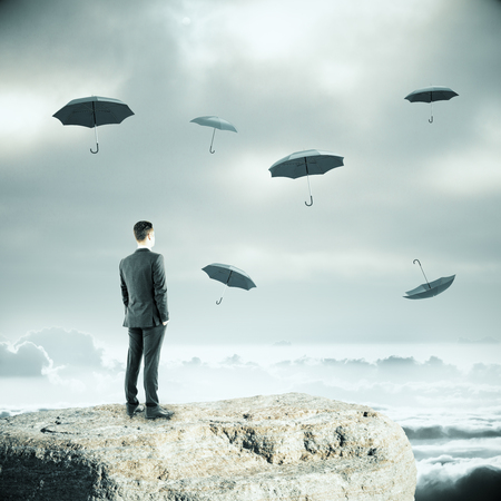 dull: Thoughtful businessman standing on cliff and falling umbrellas on dull sky background. Safety concept