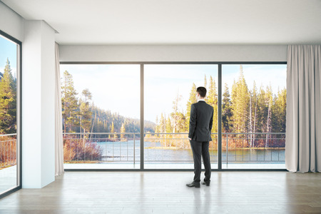 unfurnished: Businessman in unfurnished concrete interior with panoramic windows and landscape view. 3D Rendering