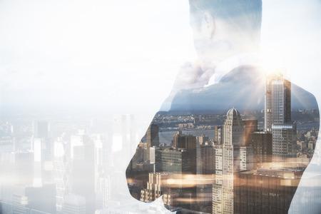 都市の背景に思いやりのある実業家を背面します。二重露光。研究コンセプト 写真素材