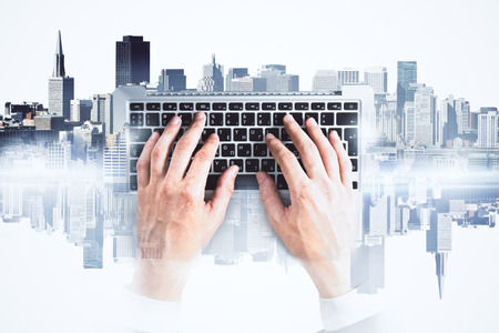 Hands using abstract keyboard on bright city background. Technology concept. Double exposure