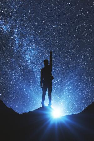 Opinião traseira o homem de negócios no espaço que alcança para fora para as estrelas. Conceito de sonhos Foto de archivo
