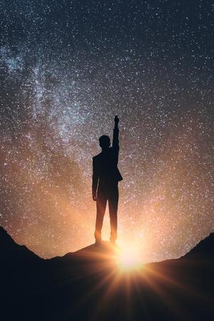 Vista posterior del hombre en el espacio que alcanza hacia fuera para las estrellas. Concepto de los sueños Foto de archivo - 69336615