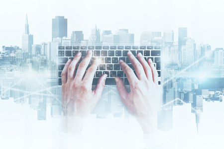 business connection: Hands using abstract keyboard on white city background. Technology concept. Double exposure Stock Photo