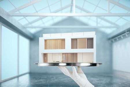 ownership: Hand holding silver trey with modern house in concrete interior. Property concept. 3D Rendering