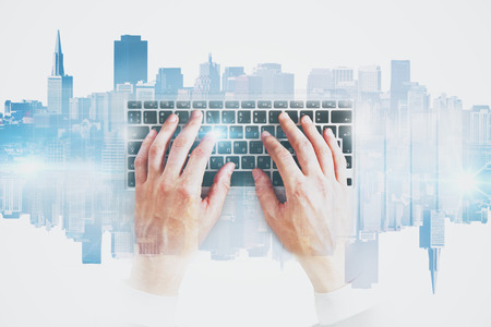 double exposure: Hands using abstract keyboard on light city background. Technology concept. Double exposure
