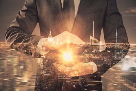 Abstract image of businessman holding light on city background. Double exposure