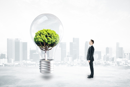 Thoughtful businessman looking at absract lamp with tree inside on city background. 3D Rendering. Growth and idea concept
