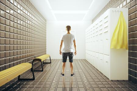 Vista trasera del hombre joven que se coloca en el interior luminoso gimnasio vestuarios. Representación 3D