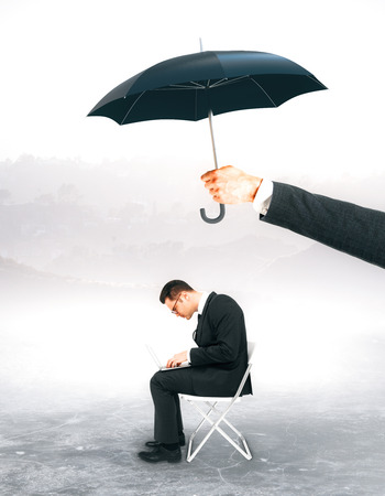 Hand holding umbrella over working businessman. Protection concept.