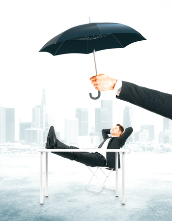 Hand holding umbrella over businessman relaxing at workplace. Safety concept. City background Stock Photo