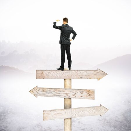Businessman standing on abstract wooden road sign. Stock Photo