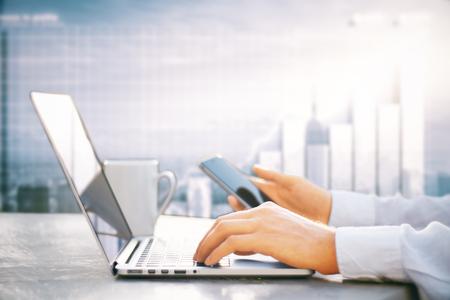 스마트 폰 및 노트북을 사용하는 사업가의 측면보기 커피 컵과 책상에 배치. 도시 및 비즈니스 차트 배경입니다. 온라인 회계 개념