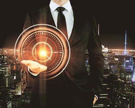 Homme d'affaires tenant une horloge orange vif abstraite sur fond de ville de nuit. Concept de gestion du temps