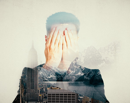 Man covering face with hands on abstract city and nature background with sunlight. Stock Photo