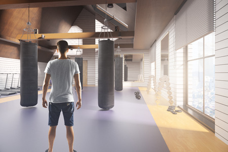 Back view of young guy in modern gym interior with equipment, city view and daylight. 3D Rendering. Stock Photo