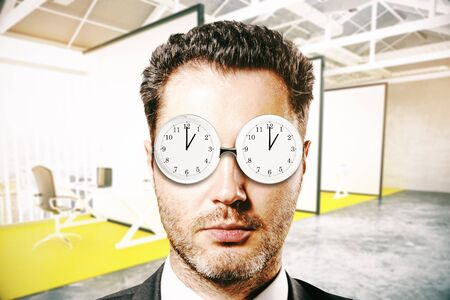Businessman with abstract clock glasses in blurry interior. Time management concept. 3D Rendering Stock Photo