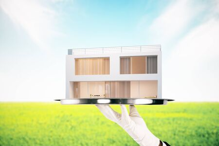 Hand in glove holding silver tray with modern house on lanbdscape background. Mortgage concept. 3D Rendering