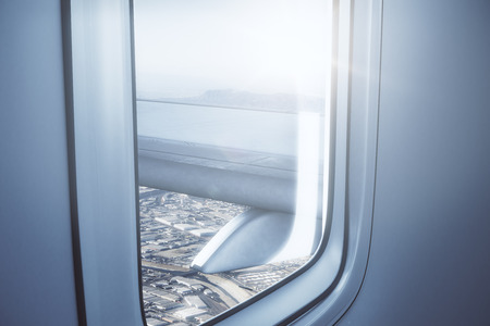 Airplane wing on city and sky background. View from illuminator. Travel concept. 3D Rendering