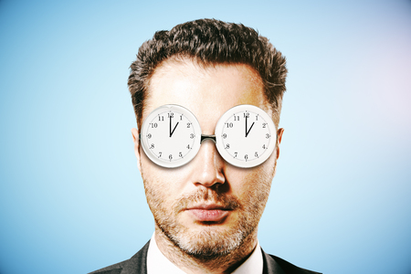 Businessman with abstract clock glasses on blue background. Time management concept. 3D Rendering Stock Photo