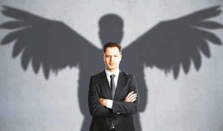 自信を持って実業家コンクリート背景に翼の影。創造性の概念