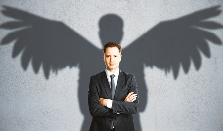 Confident businessman with winged shadow on concrete background. Creativity concept Reklamní fotografie - 73644632