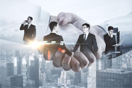 Attraktive Geschäftsleute , die Hände auf modernem Stadthintergrund rütteln . Kommunikationskonzept . Doppelbelichtung