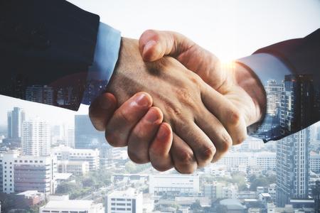 近代的な都市の背景に握手ビジネスマン。コワーキングのコンセプトです。クローズ アップ、二重露光