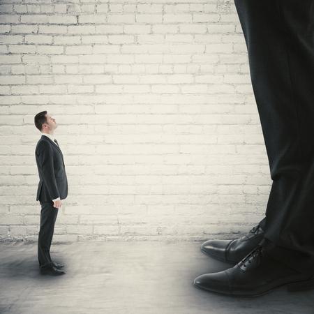 Vue de côté du petit homme d'affaires en regardant jusqu'à l'énorme. Concept de petites et grandes entreprises Banque d'images