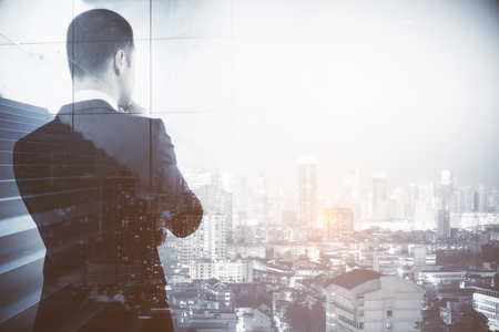 Back view of thoughtful businessman with stairs on city background. Success and growth concept. Double exposure