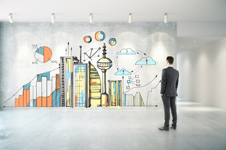 Thoughtful businessman in concrete room looking at wall with creative city sketch with business charts. Industry concept Stok Fotoğraf