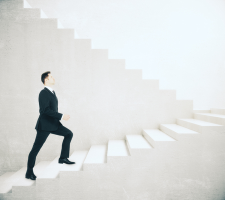 Side view of young businessman climbing concrete stairs. Success concept. 3D Rendering Stock Photo