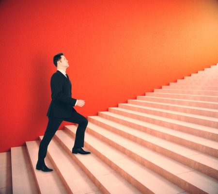 Side view of young businessman climbing red stairs. Achievement concept. 3D Rendering Stock Photo