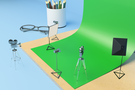 Creative tiny photo studio made out of supplies: green paper, coffee cup, pencils, glasses and other items on blue background. Closeup, 3D Rendering