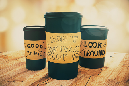 Close up of black take away coffee cups with motivational words placed on wooden table. Light bokeh background. Inspiration concept. 3D Rendering Imagens