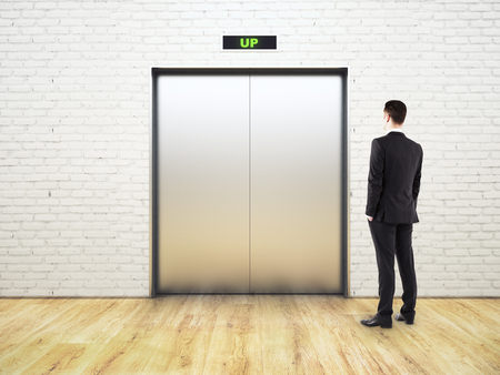 Thinking young businessman looking at silver elevator going up in light room. Success concept. 3D Rendering