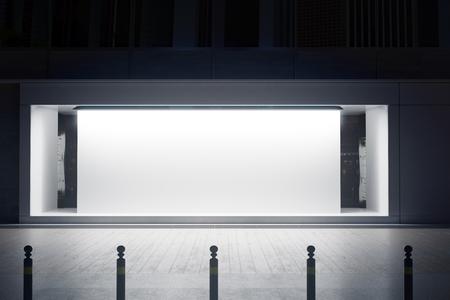 밤에 흰색 캔버스와 빈 유리 shopfront. 소매 개념입니다. 모의 3D 렌더링