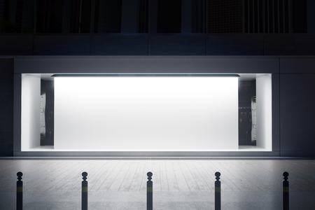 Empty glass shopfront with white canvas at night. Retail  concept. Mock up, 3D Rendering