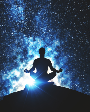 Back view of meditating man on mountain top. Space background. Yoga concept Reklamní fotografie