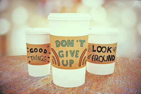 Close up of black take away coffee cups with inspirational words placed on wooden table. Light bokeh background. Motivation concept. 3D Rendering Imagens