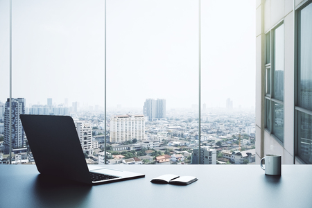 Office desktop with open laptop, notepad, coffee cup and city view. 3D Rendering