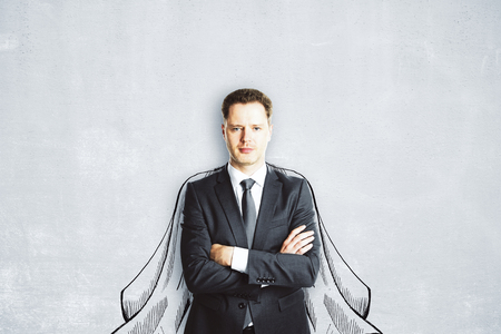 Handsome young european man with drawn cape on concrete wall background. Hero concept