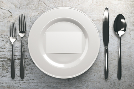 Top view of ceramic plate with empty business card and cutlery on grey wood table. Mock up, 3D Rendering Imagens
