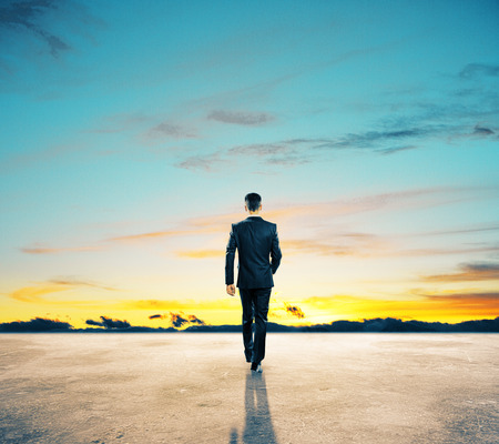 Back view of young businessman walking on concrete ground. Beautiful sky in the background. Success concept