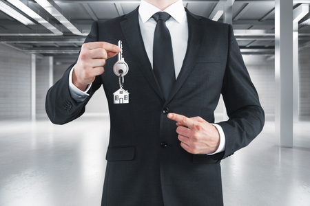 Businessman holding key with house keychain in modern interior. Real estate concept. 3D Rendering Stock fotó