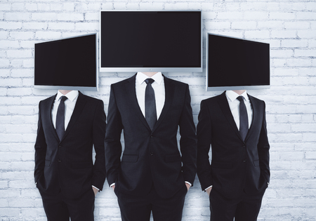Three screen headed businesspeople on brick background. Mock up Stock Photo
