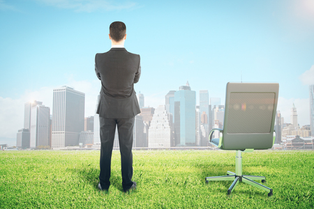 Back view of young businessman on meadow with chair looking at sunlit city. Success concept
